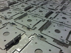 Sheet metal work projects featuring CNC punched motor end caps with folded tabs formed on the Trumpf 3000R punch press